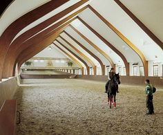 The manège, where the owner, who is a dressage champion, practices with her horses, was designed by architect René Stapels. He built it to Olympic specifications. The trusses are fashioned out of bubinga, an African hardwood.