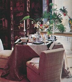 In the living room of Donghia's New York townhouse, a table was set with a Haitian cotton cloth and striped napkins, antique crystal soup bowls, Wedgwood plates, and Chinese pear boxes, which held condiments.  The table's undercloth was antique, while the raw silk slipper chairs were by Donghia/Martin Associates. September 1977 issue of Architectural Digest