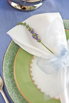Refined feminine details like white napkins tied with sheer baby blue ribbon and a floral sprig create a feeling of hospitality.
