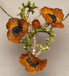 Lalique poppy pendant in gold with pate de verre and enamels; can be converted to be worn in the hair.