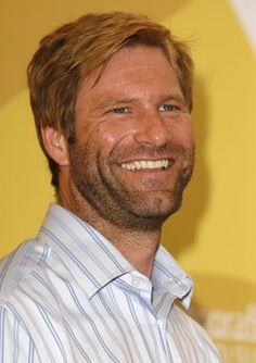 Aaron Eckhart: Great, wide smile with that charming toothy grin....that delectable 5-o'clock shadow...those piercing blue-grey eyes! And, oh, that mess of hair!