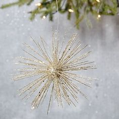 """Glitter Burst Ornament. Description says it is plastic, so it could be done with long thin straws/skewers/straight sticks (these are approx. 3"""", if the ornament is 6"""" overall) of any material. Use a styrofoam ball for the center, and glitter-spray it. Done!  But the question is whether, with cost of supplies and time, I should just pay West Elm the $6 and be done--faster."""