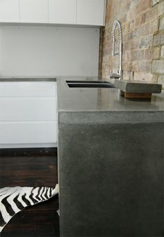 Polished concrete is a popular option for indoor furniture including bench tops, fireplaces and bathtub surrounds. Concrete Bench Top, Concrete Kitchen, Concrete Houses, Concrete Furniture, Mid Century Living Room, Kitchen Benches, Polished Concrete, Repurposed Furniture, Cool Kitchens
