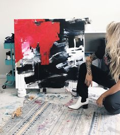 Artist Sam Rueter in her Charleston studio with a finished piece. Black white and red mixed media painting