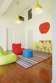 Multi-colored kids playroom with red apple art over a wall length workstation lined with yellow Tabouret kids chairs.