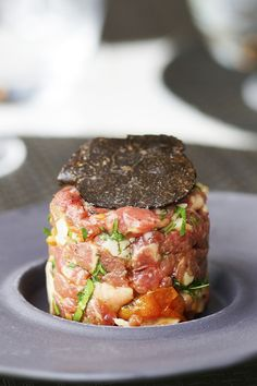 Black Angus tartare. Cubes of premium, deep red black Angus beef -- seasoned with salt and freshly cracked black pepper, then mixed in truffle oil with diced red onion and roughly chopped parsley. Garnished with grated Parmesan and thinly sliced black truffle.