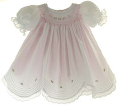 Infant girls white short sleeve smocked bishop dress smocked in pink has pink satin ribbon bows and beautiful lace trim on the sleeves and scalloped hem. Baby girls white smocked dress has pink embroidered rosettes above the hem and comes with a pink slip.