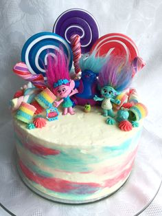 Trolls birthday cake. All buttercream icing. The top is loaded with candy, lollypops, and marshmallows. There are three layers of chocolate cake on the inside. I made this cake for my daughters fourth birthday.