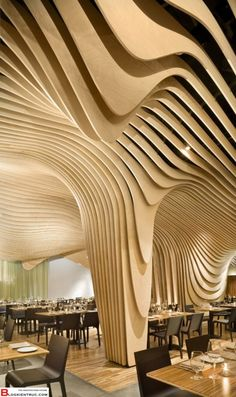 An undulating ceiling constructed from suspended wooden panels create a sense of intimacy. Some areas are more intimate than others, offering a dynamic experience for users.   Curvilinear forms were never my thing but this will always be a favorite.   Banq Restaurant by Office dA
