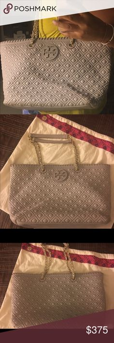 Tory Burch Marion Quilted Chain-Strap Pre-Loved. Authentic TB Quilted Gray Marion Tote. Beautiful and gently used. Gold chain strap. Magnetic Closure, center divide has zip top closure. The back of the bag has little blue discolor due to jeans. Other than that excellent conditions! Kept in dust bag. Smoke free home! Open to trade!😜 Tory Burch Bags Totes
