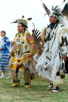 Pow Wow Dancers in Minnesota. From left to right: Jingle dress dancer, Men's Northern Traditional, Men's Fancy Feather.