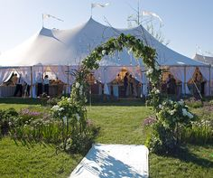 An arch of greens, hydrangeas and dangling crystals leads to a white tent housing the reception.