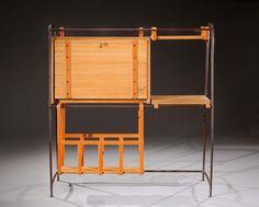 JACQUES ADNET (1900-1984) Rare cabinet à structure en métal tubulaire partiellement gainée de cuir marron piqué-sellier ouvrant en façade par un abattant découvrant un espace de rangement et présentant en partie basse un porte-revues et une tablette amovible sur le côté. Vers 1950. H : 130 cm L : 123 cm P : 37 cm Rare tubular metal cabinet  Circa 1950. H : 51 L : 52 D : 14 ½ in.