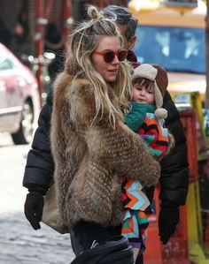 Sienna Miller in a stunning fur coat, red sunnies and messy hair