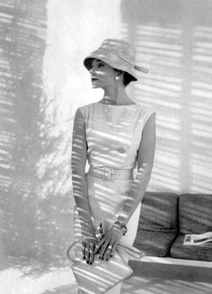 Model in sleeveless white jersey sheath, button on the side, wide leather belt, by Pierre Balmain, hat by Legroux, handbag by Jean Pax, photo by Pottier, 1959