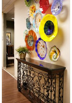 """Via Houzz: """"Glass plates needn't be purchased all at once. I like how this grouping has a collected-over-time aesthetic.  While there are many ways to hang sculptural art, these glass plates have a conical base that fits into a pipe-like bracket. Screws on the sides of the pipe portion are tightened to anchor the piece in place."""" Plates: Viz Glass"""
