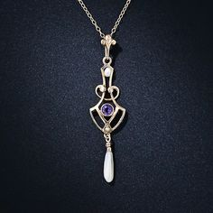 A sweet and lovely Art Nouveau lavaliere necklace - circa 1900 - delicately crafted in openwork 10 karat gold and featuring a round faceted amethyst and a pair of freshwater pearls. The pendant measures 2 inches long, the chain measures 17 inches.