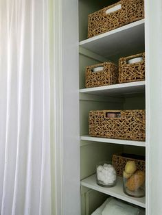 Removing bulky linen closet doors helped opens up a small area and keeps items accessible. Corralling like items ? wash cloths, cosmetics, etc. -- in baskets prevents the open storage from looking cluttered.