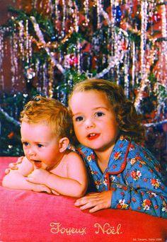 Joyeux Noël - Une fillette et son petit frère qui baille allongés sous le sapin de Noël décoré de guirlandes - 1956 (from http://mercipourlacarte.com/picture?/1418/)