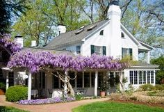 I absolutely love this combined cottage/farm house/french country look.  The wisteria reminds me of lavender.  The only think it needs is a breezeway connecting the carriage house/garage to the main house.