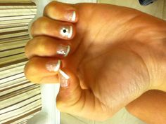 This nail design is French with sparkles and a flower with a stone on the ring finger how fab