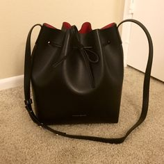 Mansur Gavriel Bucket Bag (Black/Flamma) *Unsure of whether to sell or not, hence the high price. Comment below if interested and I will consider!* Mansur Gavriel bucket bag with black exterior and Flamma (red) interior. Does not come with detachable wallet/pouch, as I am keeping that. Bought on Net-a-porter for $595. Like new condition, used 5 times max. This is the largest size of the bucket bag. Sold out on Mansur Gavriel website. Mansur Gavriel Bags Shoulder Bags