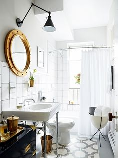 Stylish bathroom with a gold mirror, a black wall sconce, and a small dresser