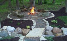 Backyard fire pit with landscaping. Rock path and boulders as seats.