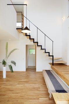 吹抜けのリビングに取付られた階段。如何にシンプルにそして機能的に。二階ホールの手摺壁に取付られたブラケット照明とのライン合わせに気を配り、ブラック塗装で統一感を出しました。
