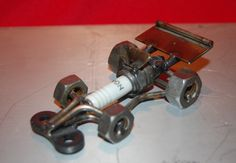 I have made another Indy/Formula One type spark plug racing car. I have another one listed on here which is larger. This little car would make a great gift for any occasion.  Thanks for looking at my art and come back often.