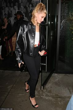 Hailey Baldwin wearing a black Leather jacket, with a white knotted crop top and black J Brand high waisted jeans. Her shoes are made by Givenchy Visit the site to buy this outfit! #ootd #celebrity #outfit #lookbook