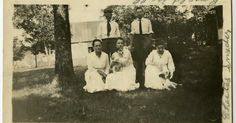 Laura Ingalls Wilder, kneeling, front right, patting small dog. Photo taken at Rocky Ridge Farm with members of the Snyder family (notes penciled on border)...