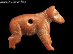 SUMERIAN RED STONE AMULET  Perhaps in the form of a canine, the eyes drilled, the back perforated for suspension.  Late Uruk-Jamdat Nasr Period, ca. 3300-2900 BC. - Iraq
