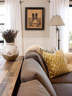 Chevron throw pillows bring a pop of color into this transitional living room, while the reclaimed wood console table adds a rustic element to the space. The lavender-filled Tuscan cachepot and framed Old World artwork add a European feel.