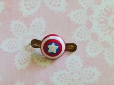 This hair clip features Marvel's Captain America's shield, made out of clay and hand painted.