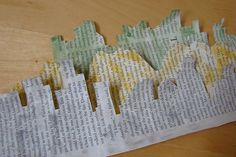 Strips from an article in a magazine. Cut out in the shape of buildings and mountains and painted with watercolour. They will be part of a mixed media piece in a traveling art journal about international mail.