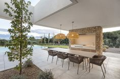 A lovely outdoor setting from Single Family House in Montras by Dom Arquitectura   HomeAdore www.fiori.com.au #outdoorkitchen #bbqdesign #bbqarea #outdoorkitchenandbbq #entertainingarea #entertainingathome Outdoor Tables, Outdoor Spaces, Outdoor Decor, Porches, Modern Outdoor Kitchen, Dry Stone, Hip Roof, Wooden Ceilings, Story House