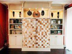 Designer Meg Caswell creates an entertainment center with traditional moldings and worldly charm. Tiled doors hide the TV when not in use, while the shelves are filled with finds from the homeowners' travels.