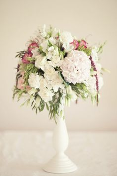 some centerpieces can be on pedestals.  Like the idea of more loosely arranged than this.