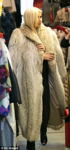 Style icon: The newly-platinum star tried on a dramatic fur coat in the shop, which made her resemble animated character Cruella De Vill (right)