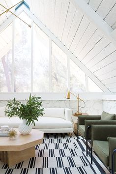 white A frame, monochrome striped rug. green armchairs, wooden coffee table, white sofa, gold lamp
