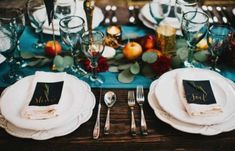 a teal table runner and glasses, copper candle holders and burgundy and orange touches for a fall table