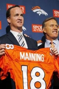 New Denver Broncos quarterback Peyton Manning holds a Broncos jersey next to vice president of football operations John Elway during an NFL football news conference at the Broncos headquarters in Englewood, Colo.,  on Tuesday, March 20, 2012. (AP Photo/David Zalubowski)