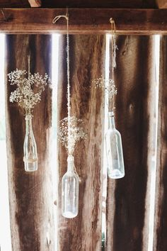 Doesn't have to just be rustic -- hanging bottles with baby's breath... On http://www.StyleMePretty.com/southeast-weddings/2014/03/26/barn-wedding-at-high-point-farms/  John Shim Photography - johnshim.com