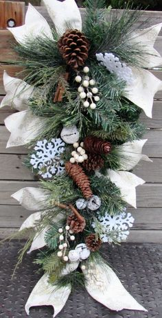 This teardrop is anchored by a greenery teardrop adorned with snowy greenery, pine cones, white berries, snowy jingle bells, sticks and snowflakes. Ties of cream ribbon with shimmery damask pattern throughout. Beautiful for Christmas and Winter!  Measures- 3 long 12 wide