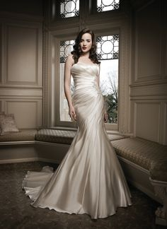 Justin Alexander wedding dresses style 8687 This soft strapless gown is made of regal satin and features  asymmetrical pleating into a beaded side yoke. The back of the dress is  finished off with a chapel length train and has satin and beaded buttons  that cover the back zipper.