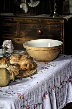 French embroidered tablecloth, old ochre-hued pottery mixing bowl ~ and, of course, a brioche on the breadboard!