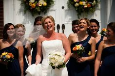 Bridesmaids :  navy blue dresses with yellow, white and orange bouquets