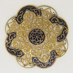 Intricately pierced openwork, antique brass button with champleve enamel highlights at center and edges.