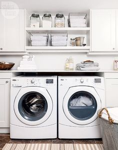 White laundry room with metal accents boasts white shaker cabinets adorning polished nickel knobs flanking built in shelves holding glass storage containers beside vintage metal bins while below a white front loading washer and dryer sits under a white marble countertops on brown flower tiles covered in a striped beige rug sat below a metal laundry basket.